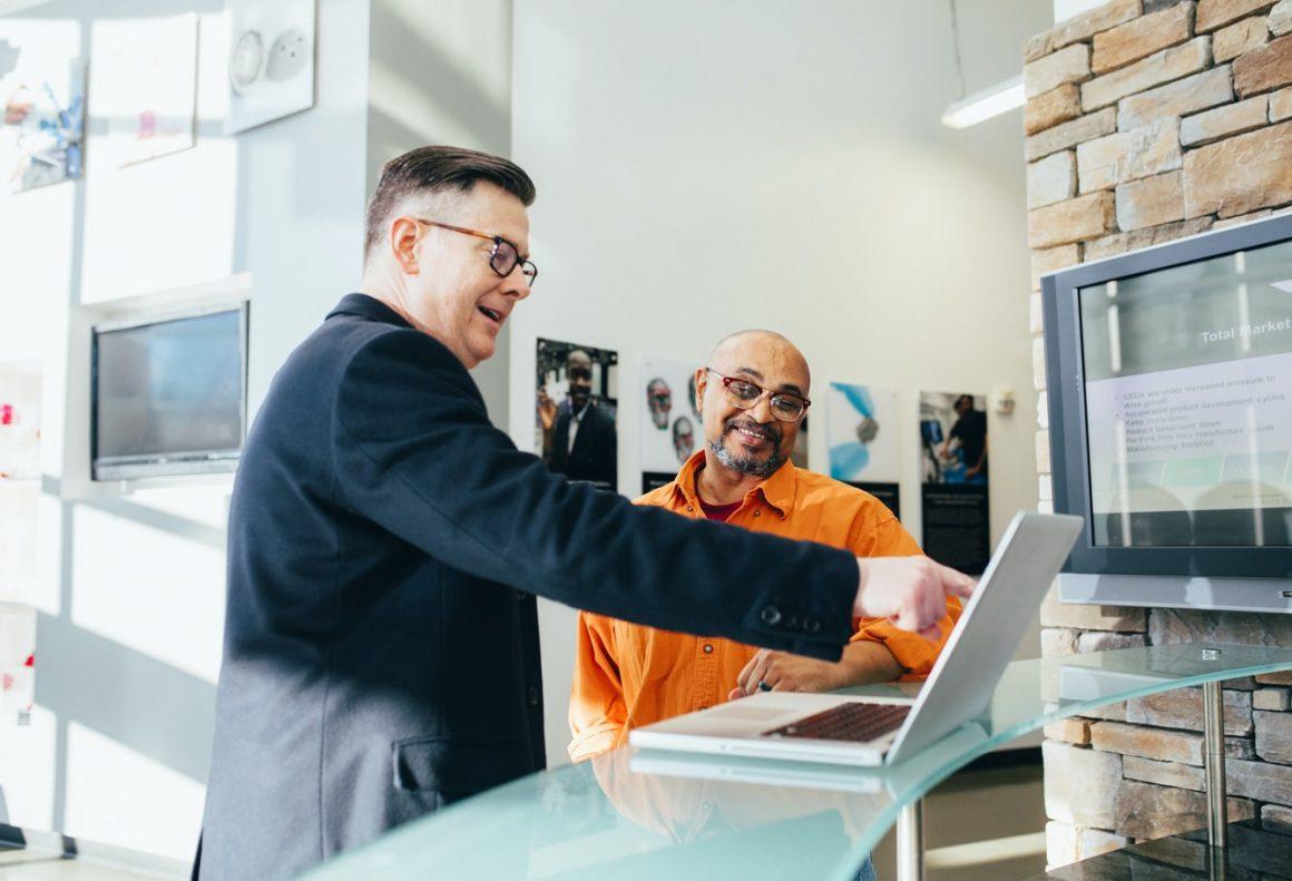 two men happily checking laptop