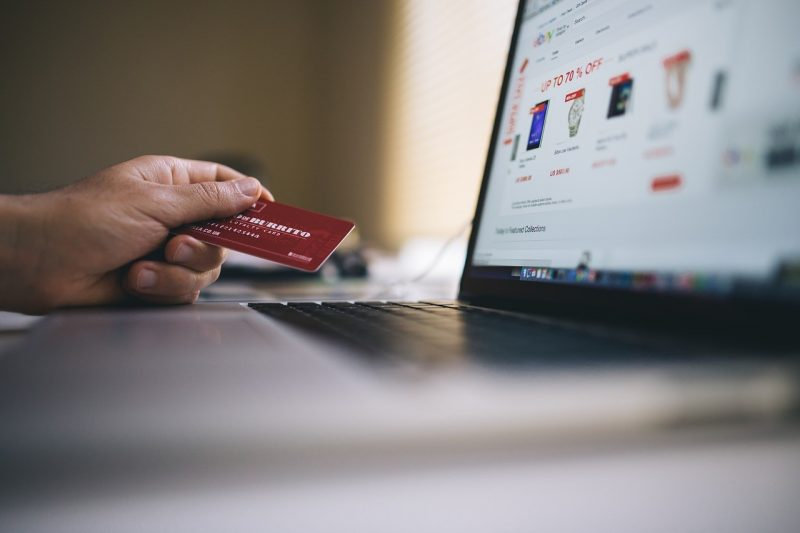 man holding credit card and laptop