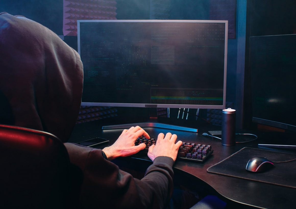 man with a hood is typing on a computer