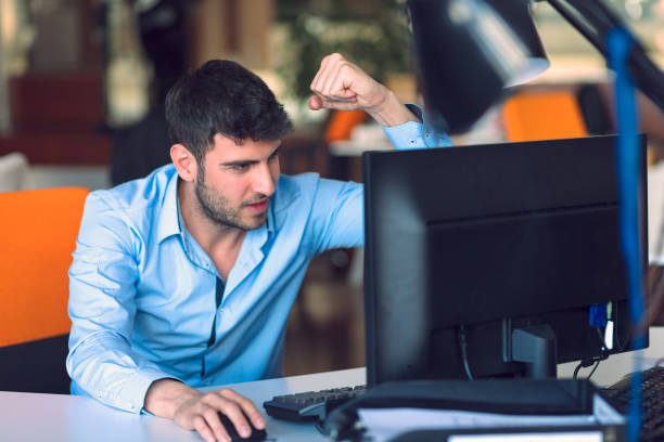 a man exclaiming in front of a computer